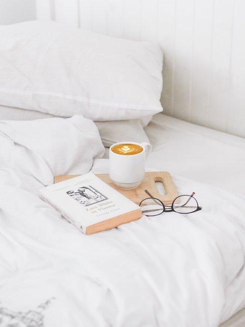 cama con libro cafe y gafas