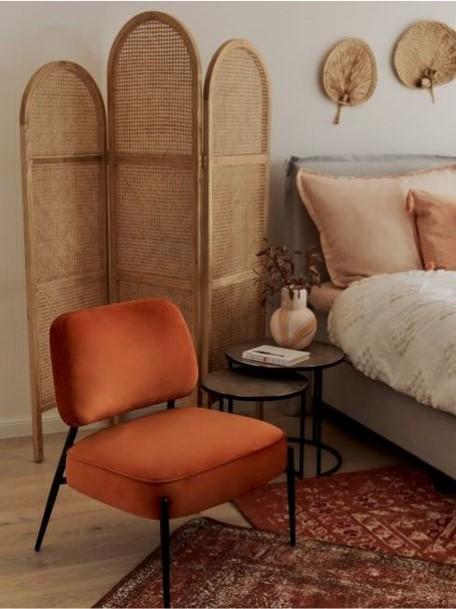 un sillon un biombo y una cama