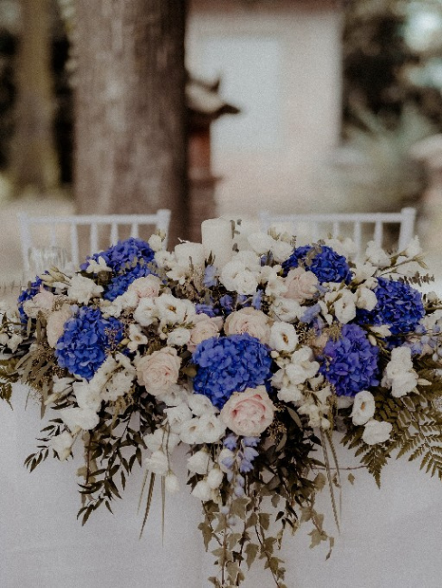 Centro de flores blancas y azules de boda