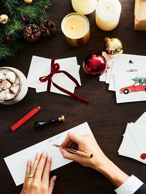 mujer escribe una postal de navidad