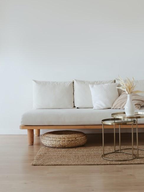 salon con un sofá blaco y unas mesas auxiliares de latón