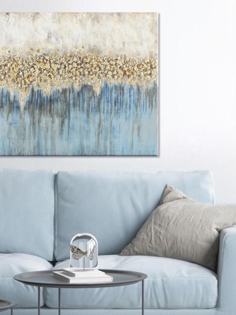cuadro en un salón sobre un safá azul