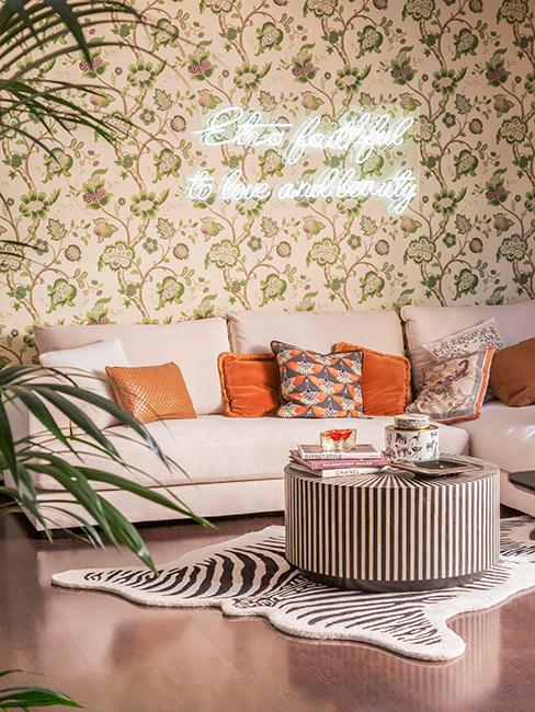 salon rétro avec tapisserie à motif, néon, canapé beige, coussins orange et tapis imprimés zèbre