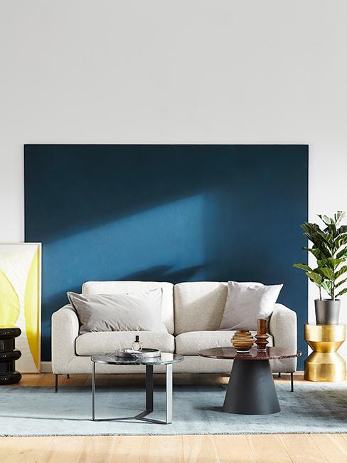Canapé beige avec mur bleu foncé et cadre jaune citron, tables basses noires