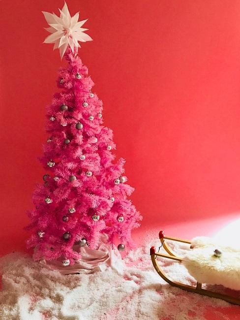 Sapin de Noël rose sur un mur rouge, une luge déco devant