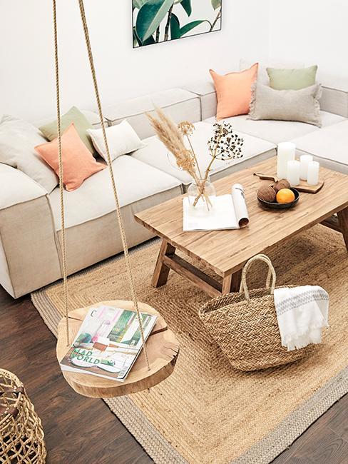 Salon avec canapé beige, table basse en bois, balancoire en bois, tapis en jute et panier en osier