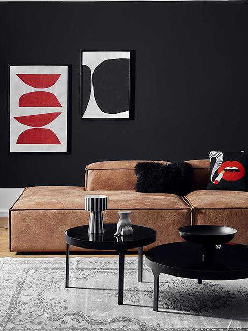 Salon avec canapé en cuir, tables basses noires, mur noir et cadres rouge et noir