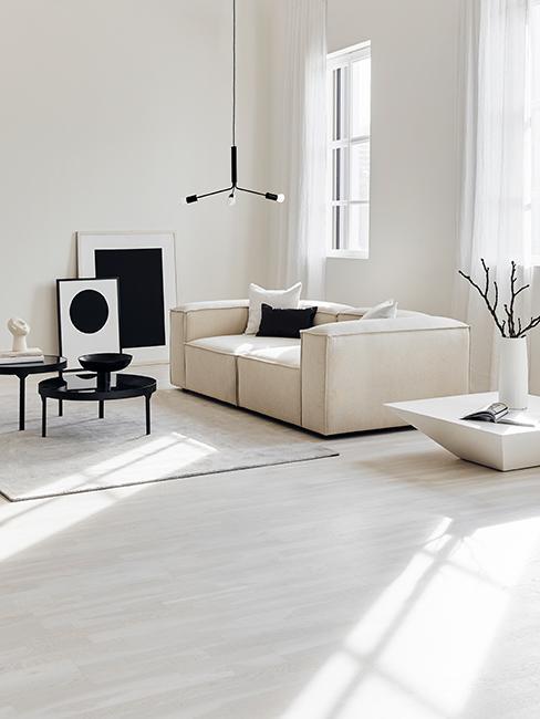 Salon avec canapé beige, tables basses noires, cadres posés au sol et suspension en métal