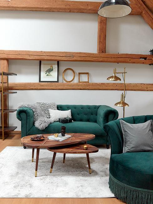 Salon style rustique chic avec canapé vert sapin, tables basses en bois et poutres apparentes