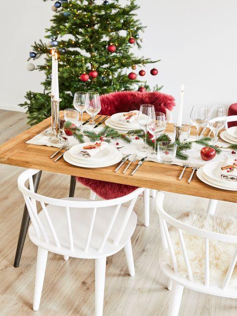 sapin de noel decore, table en bois massif, chaises scandinaves blanches, table decoree avec vaisselle blanche, coussin de chaise fourrure synthetique rouge