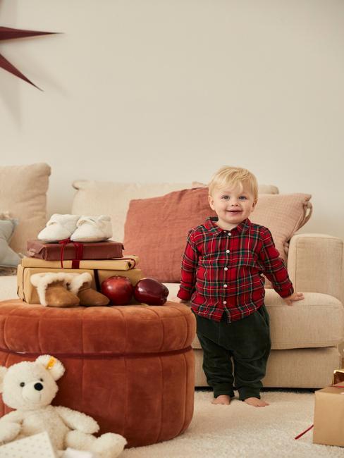 Petit garçon dans un salon avec des jouets sur un grand pouf rouge