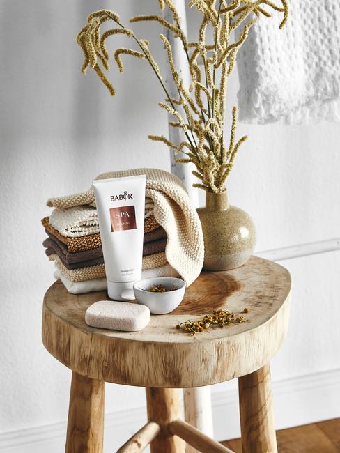 Plante en vase sur un tabouret en bois avec des crèmes dans une salle de bains