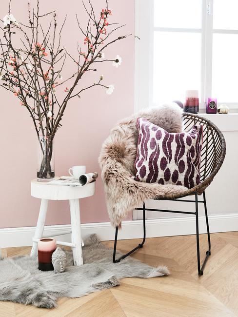 Coin lecture avec fauteuil, tabouret blanc à 3 pattes et mur peint en rose