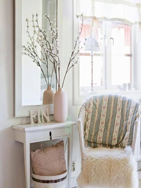 Hall d'entrée romantique couleur rose poudre et blanc avec petit fauteuil et console en bois vase et fleurs sechées