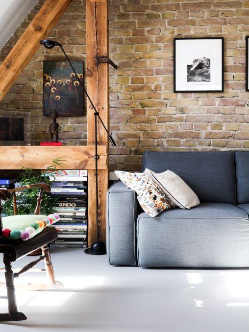mur en briques, grenier, canape gris, cadres sur le mur, poutres en bois
