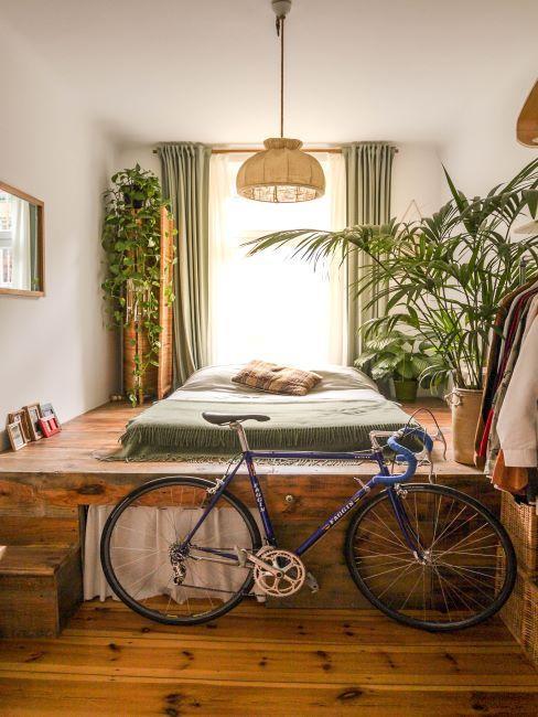 lit sur un espace sureleve, rideaux verts, plantes, velo