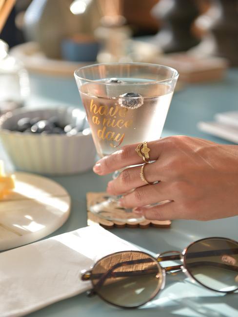 The Kharites - main de femme avec bijou prenant un verre