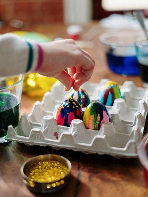Main d'enfant qui décore des œufs de Pâques