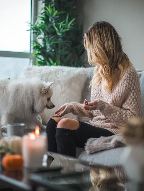 femme assise sur un canapé beige et son chien vient près d'elle