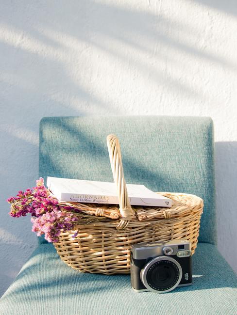 Panier en osier avec bouquet de fleurs et appareil photo posés sur une chaise