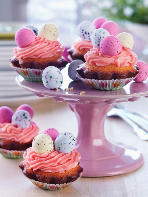 Cupcakes avec œufs de chocolat de Pâques sur un présentoir un gâteaux rose