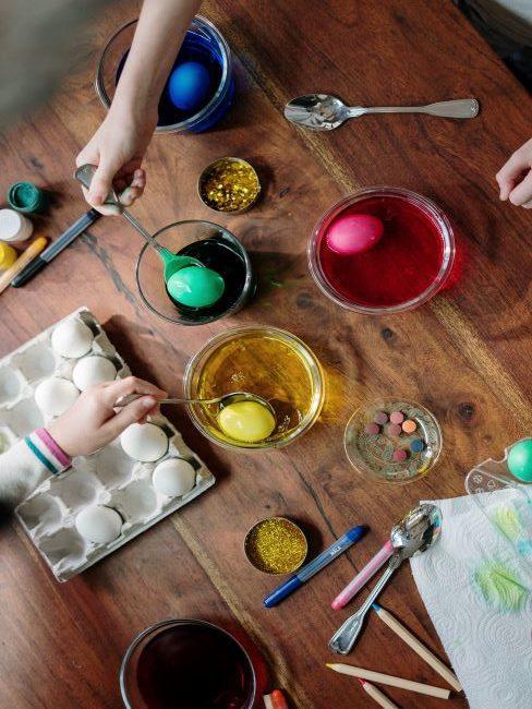 Personnes coloriant des œufs dans des bols avec différentes couleurs de peinture