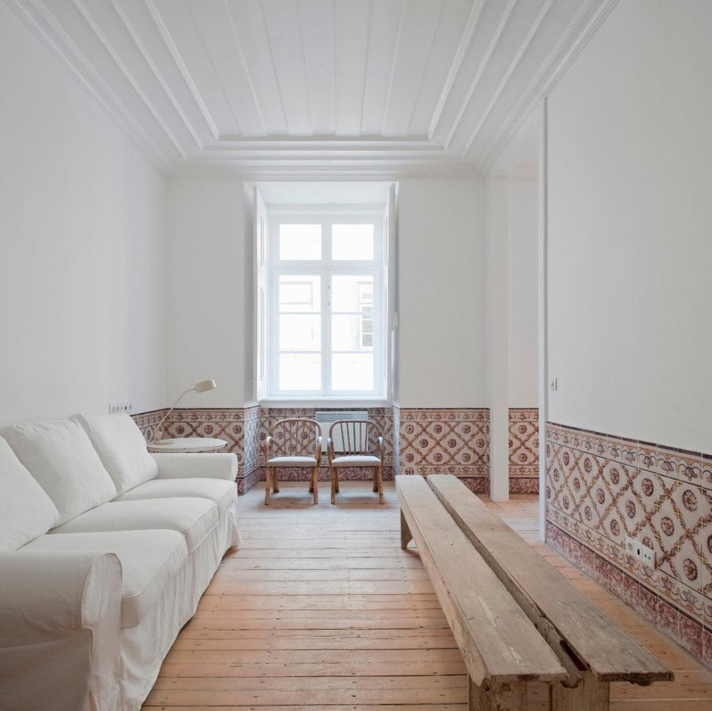 Mur avec détails de carreaux en céramique et grand canapé blanc moulures au plafond