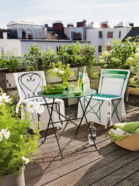 table ronde pliable en metal avec deux chaises de differents styles sur une terrasse en bois, tonalite verte
