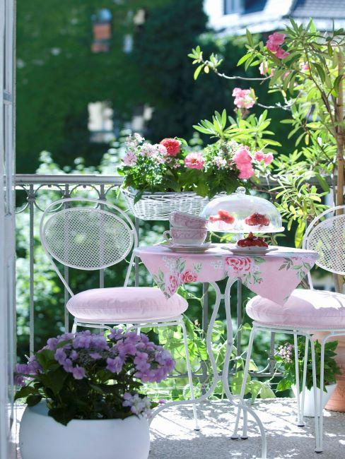 balcon fleuri avec petite table rond en metal blanc, deux chaises et textiles rose tres clair