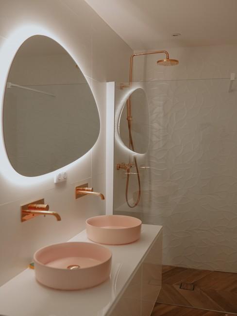 Salle de bain blanche avec miroirs ovals et vasques roses