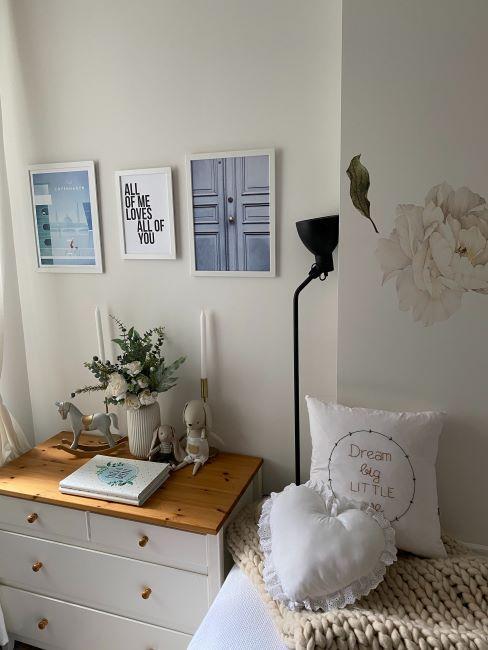 chambre aux tons clairs, n coussins blancs, commode blanche, cadres sur un mur blanc, un luminaire noir