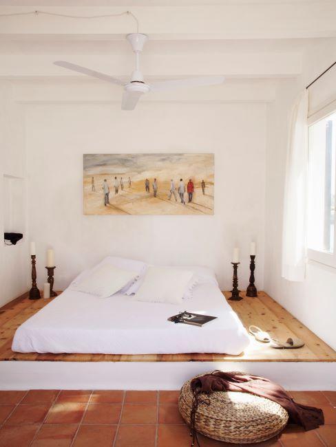chambre a coucher avec un matelas pose par terre, sur un podium en bois, dans une chambre aux murs blancs, tableau sur le mur et bougeoirs des deux cotes du lit
