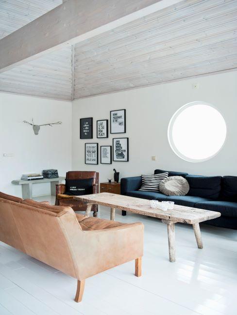 salon avec canape en cuir clair, canape en tissu fonce et table basse longiligne en bois