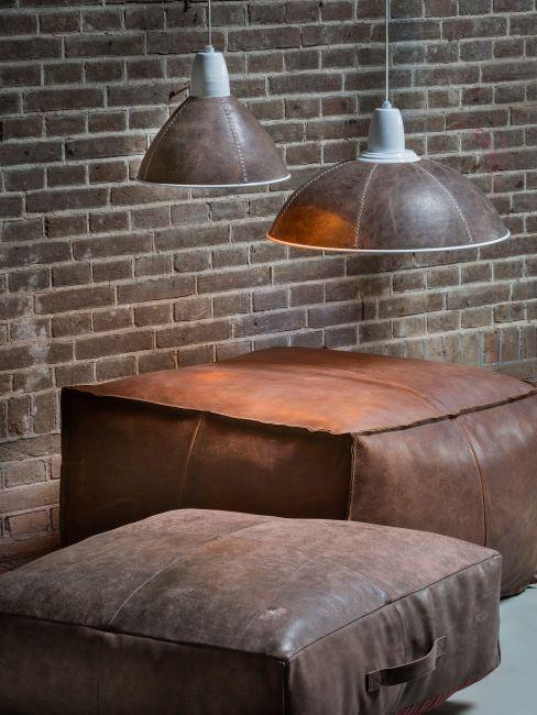 Deux poufs en cuir, mur en brique et suspensions en cuir