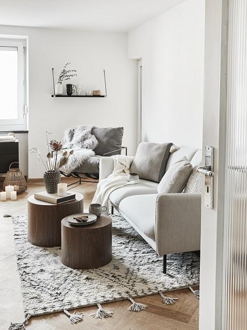salon minimaliste, blanc gris, avec tables basses en bois, murs blancs, tapis sobre