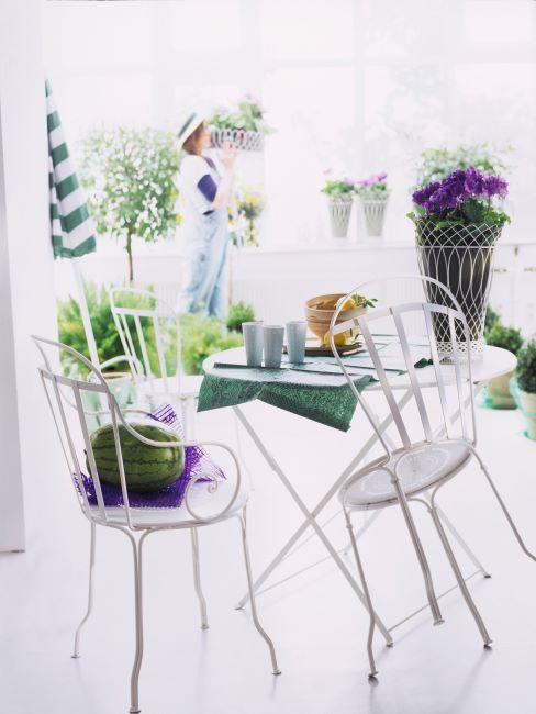 salon tres clair avec table et chaises blanches, des fleurs disposees partout