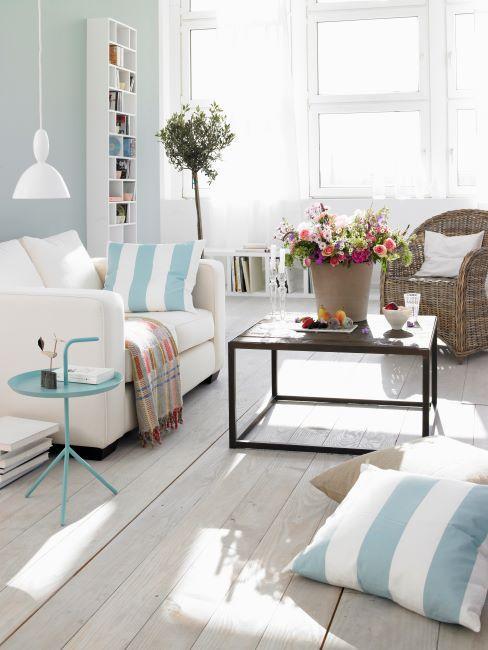 salon blanc et bleu clair, canapé blanc, coussins rayures bleues et blanches, sol en bois vieilli, table basse design avec un bouquet de fleurs pose dessus, fauteuil en rotin avec coussin blanc