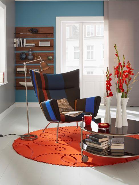salon design, couleurs vives, fauteuil papillon, a accoudoirs, tapis orange, table basse avec roulettes, avec trois vases blancs et fleurs rouges , liseuse
