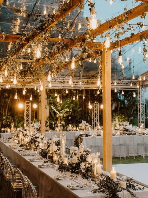 Table de mariage en extérieur décorée avec des guirlandes lumineuses