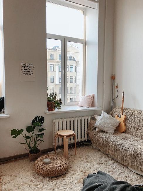 salon haut murs, fenêtre, tapis moelleux, canapé, guitare, tabouret et plantes vertes