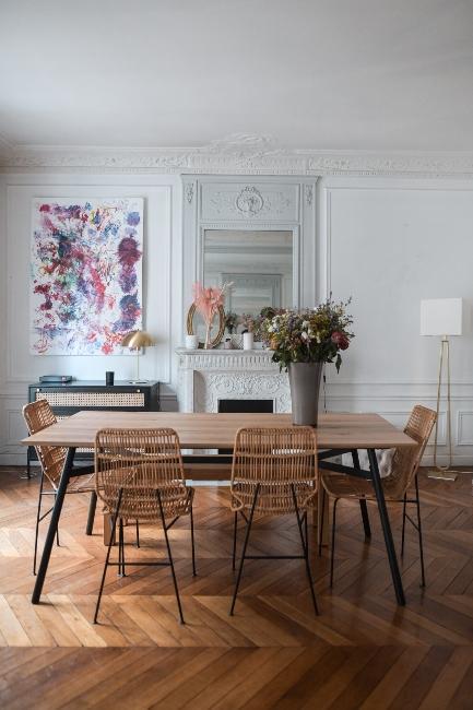 salle à manger avec table en bois et chaises en osier dans appartement parisien dans appartement trendy de Dressingleeloo