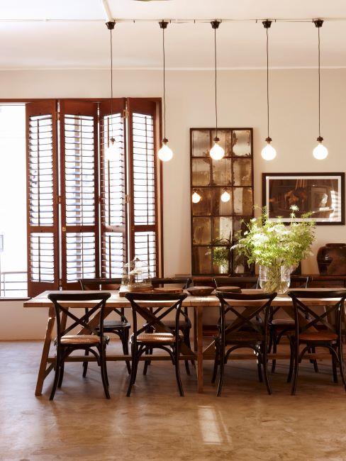 salle à manger industrielle avec grande table en bois, chaises rustiques, déco en métal brossé et suspension industrielle