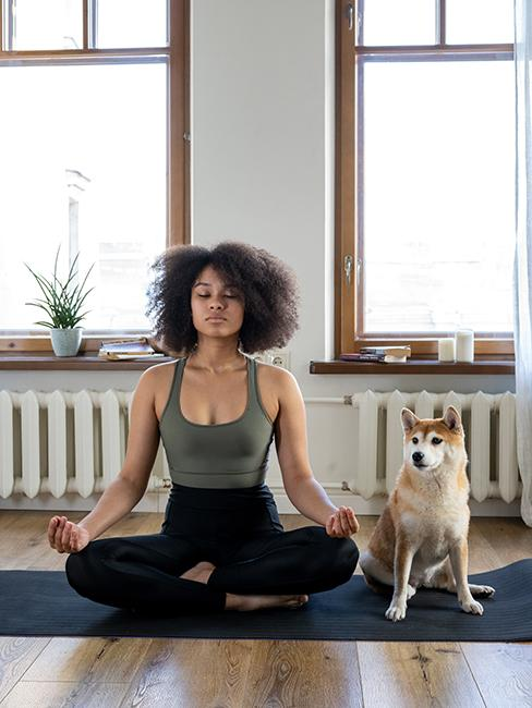Femme entrain de pratiquer une posture de yoga avec son chien