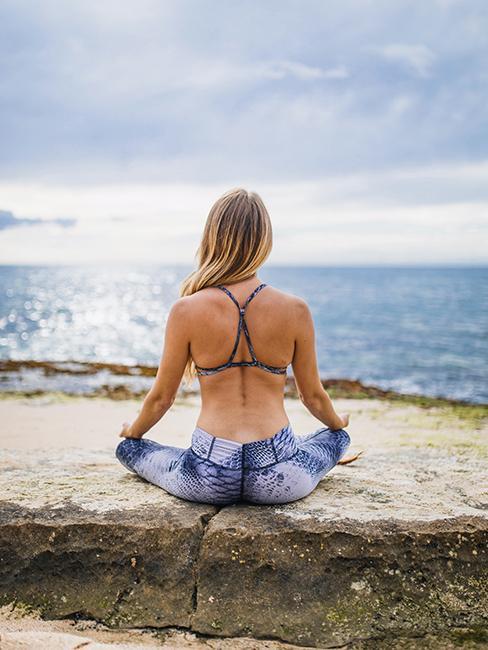 Femme entrain de pratiquer une posture de yoga sur la plage