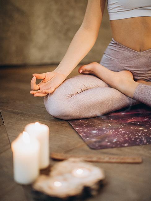 Personne entrain de méditer avec bougies et encens