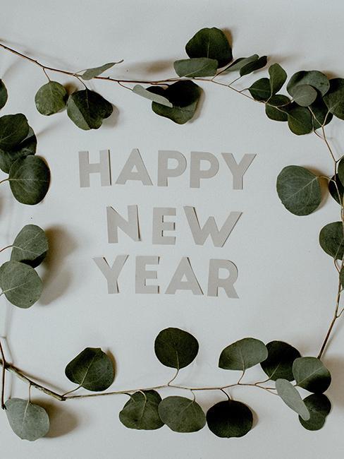 Message happy new year en lettre blanche et décoré avec des feuilles