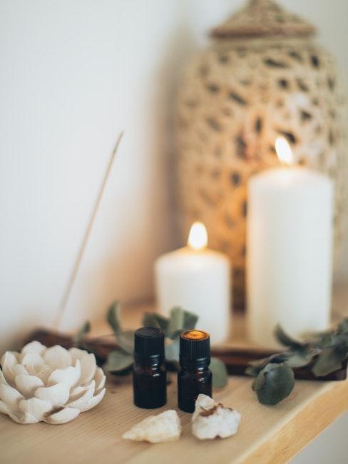 deux bougies blanches, flacons d'huiles essentielles, incens et déco boho sur étagère