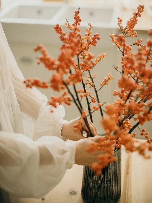 femme décorant son intérieur avec des fleurs d'automne oranges dans un vase en verre foncé