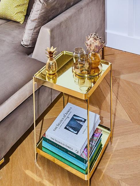 table d'appoint rétro dorée avec magazines et accessoires déco