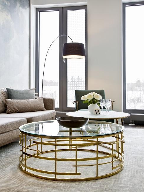 salon mid-century avec table basse dorée à plateau en verrre, canapé beige et lampadaire arc